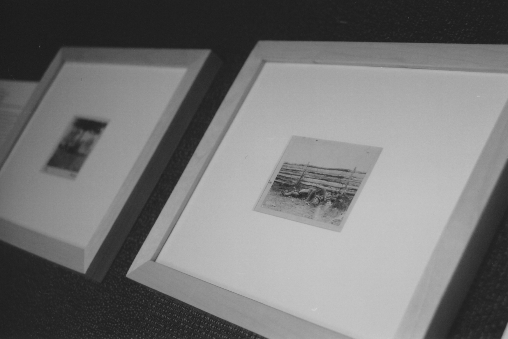 Photographs in the exhibit wait on the floor to be hung