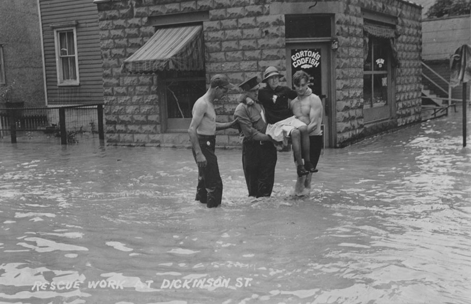 Three man carry a woman from flood waters.