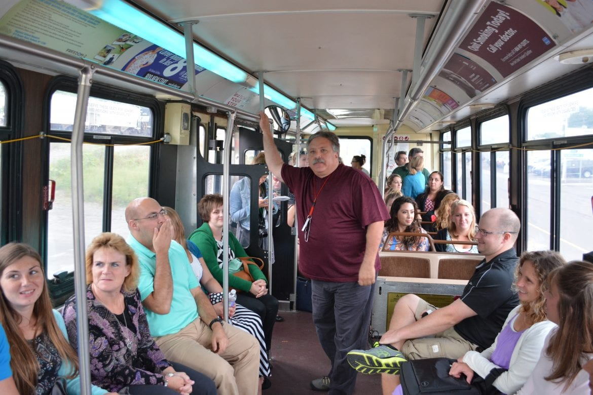 Larry Kassan leads new teachers on a bus tour of the Binghamton City School District.