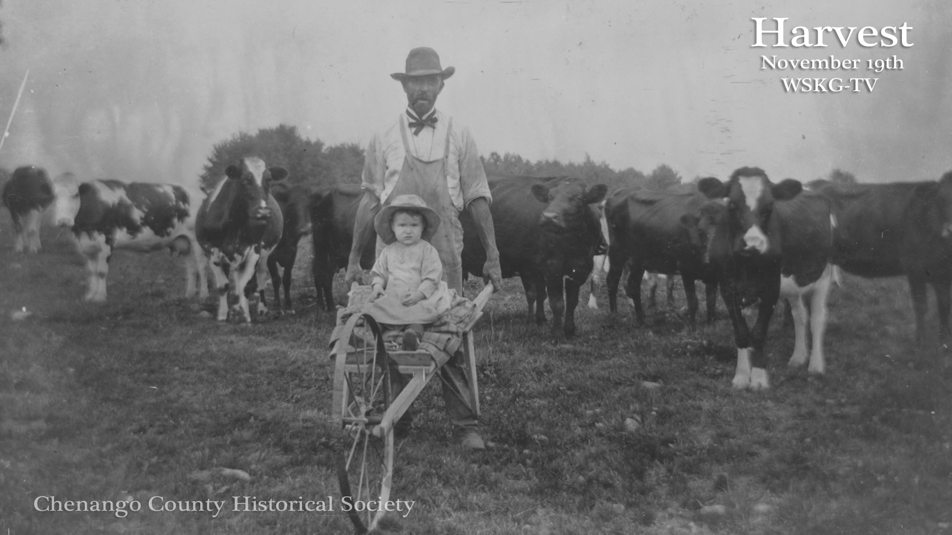 A farmer takes his daughter for a ride on a hand cart
