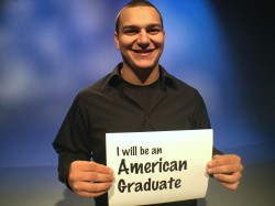 teen boy holding american graduate sign