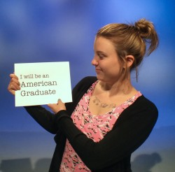 teen girl holding american graduate sign