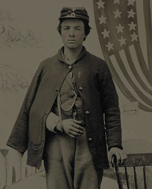 Unidentified soldier in uniform with arm in sling in front of painted backdrop showing military camp and American flag. Library of Congress.