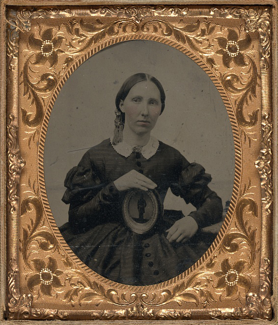 Unidentified woman wearing mourning brooch and displaying framed image of unidentified soldier.