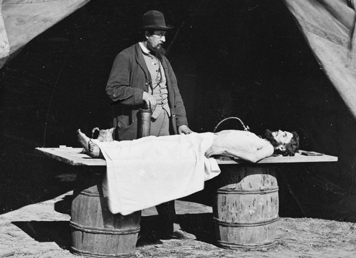 Unknown location. Embalming surgeon at work on soldier's body.