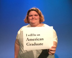 teen girl holding 'i will be an american graduate' sign