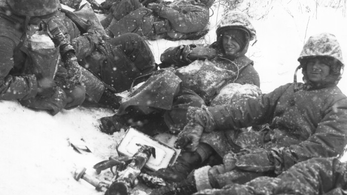 Men of a U.S. Marine mortar squad rest at the side of a snowy road during their withdrawal from the Chosin Reservoir, North Korea. (Dec. 8th, 1950)
