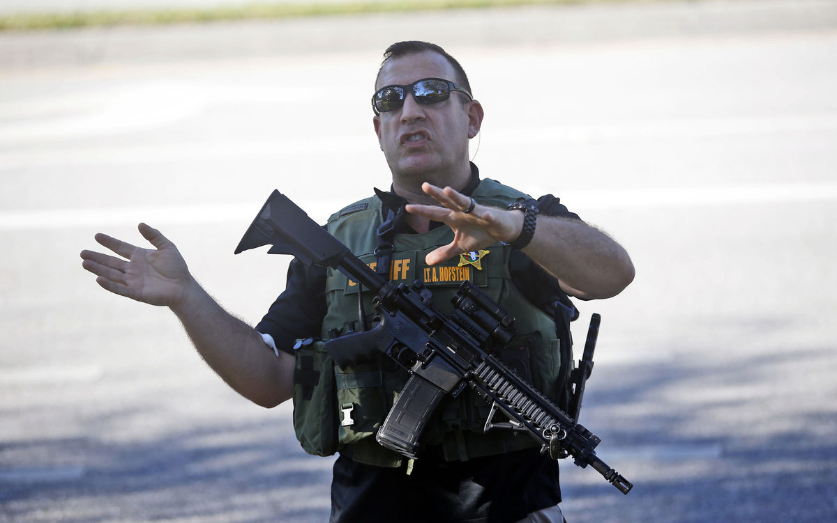 A law enforcement officer tells anxious family members to move back.