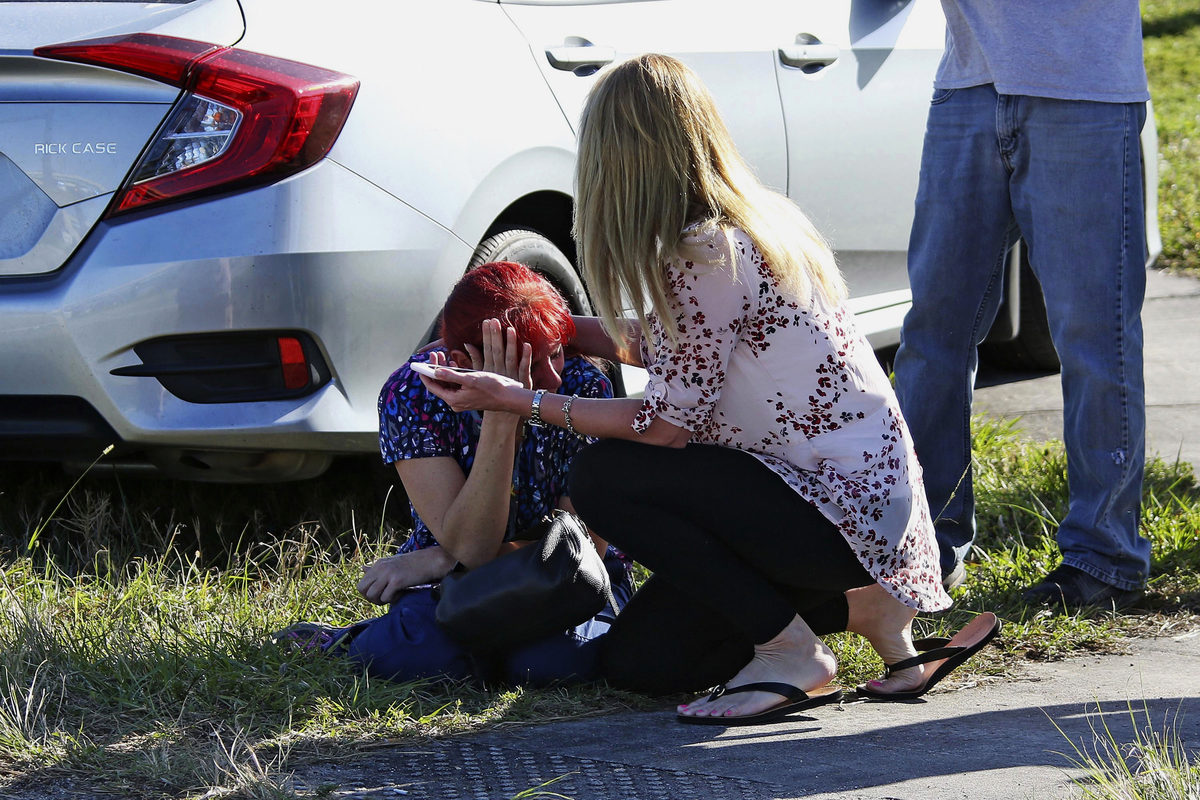 A woman consoles another as parents wait for news.