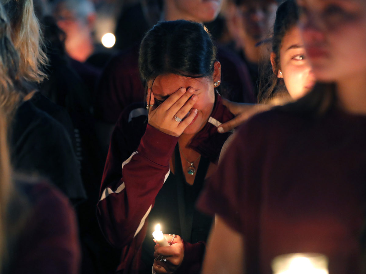 A woman cries during a candlelight vigil for the victims of the Wednesday shooting at Marjory Stoneman Douglas High School, in Parkland, Fla., on Thursday.