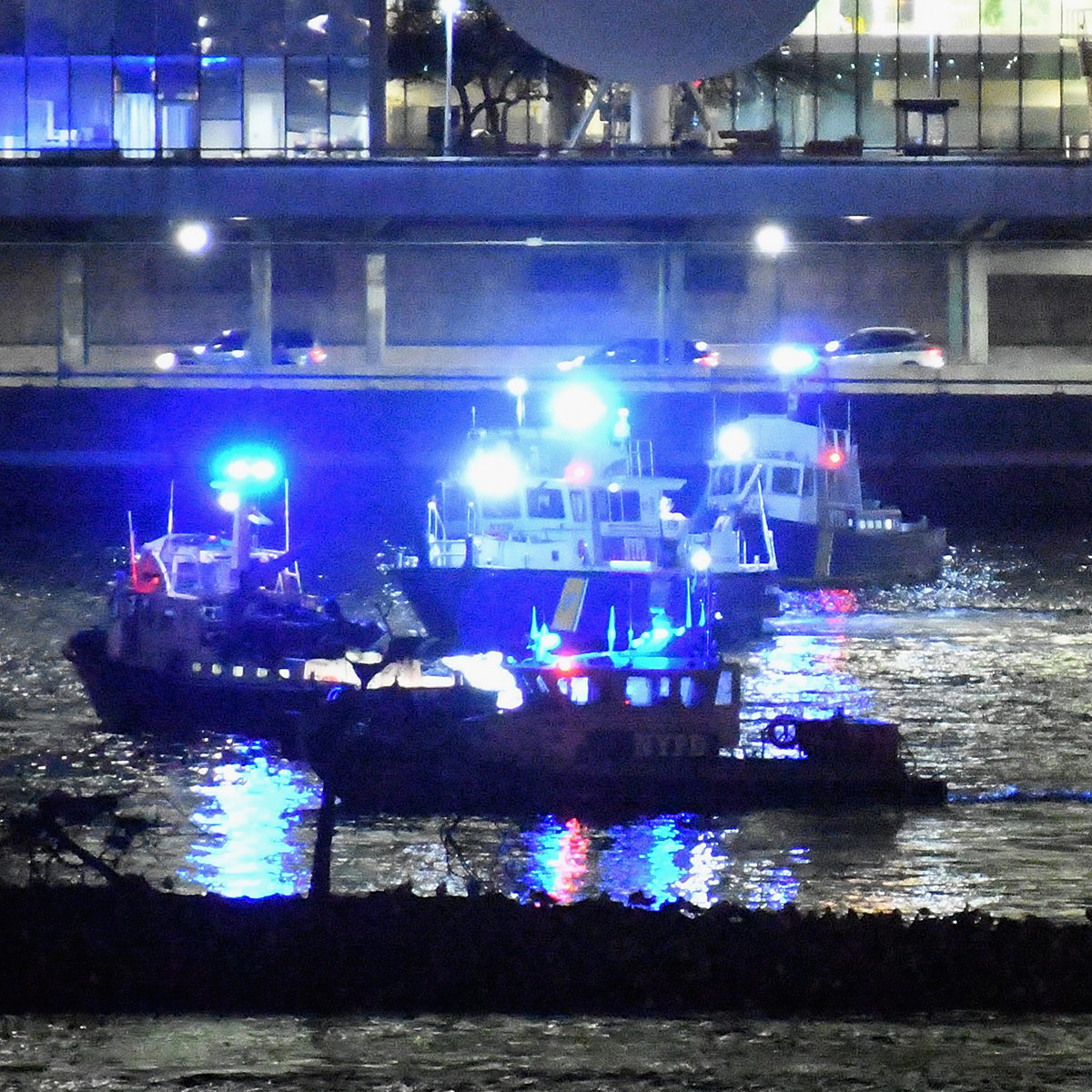 Police and firefighters respond to a helicopter crash into New York City's East River on Saturday evening that left two people dead and three others critically injured.