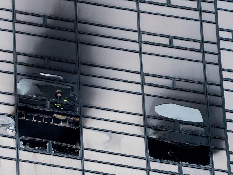 A firefighter looks out from the window of a damaged apartment in Trump Tower in New York on Saturday.