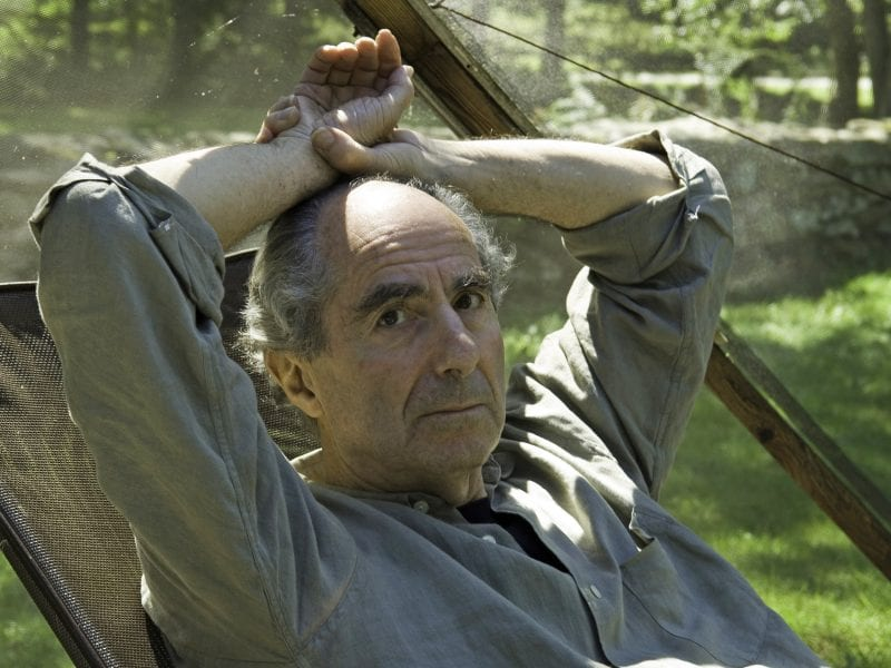 Famed novelist Philip Roth sits inside a screened tent at his home on Sept. 5, 2005, in Warren, Conn. Roth died on Tuesday. He was 85.