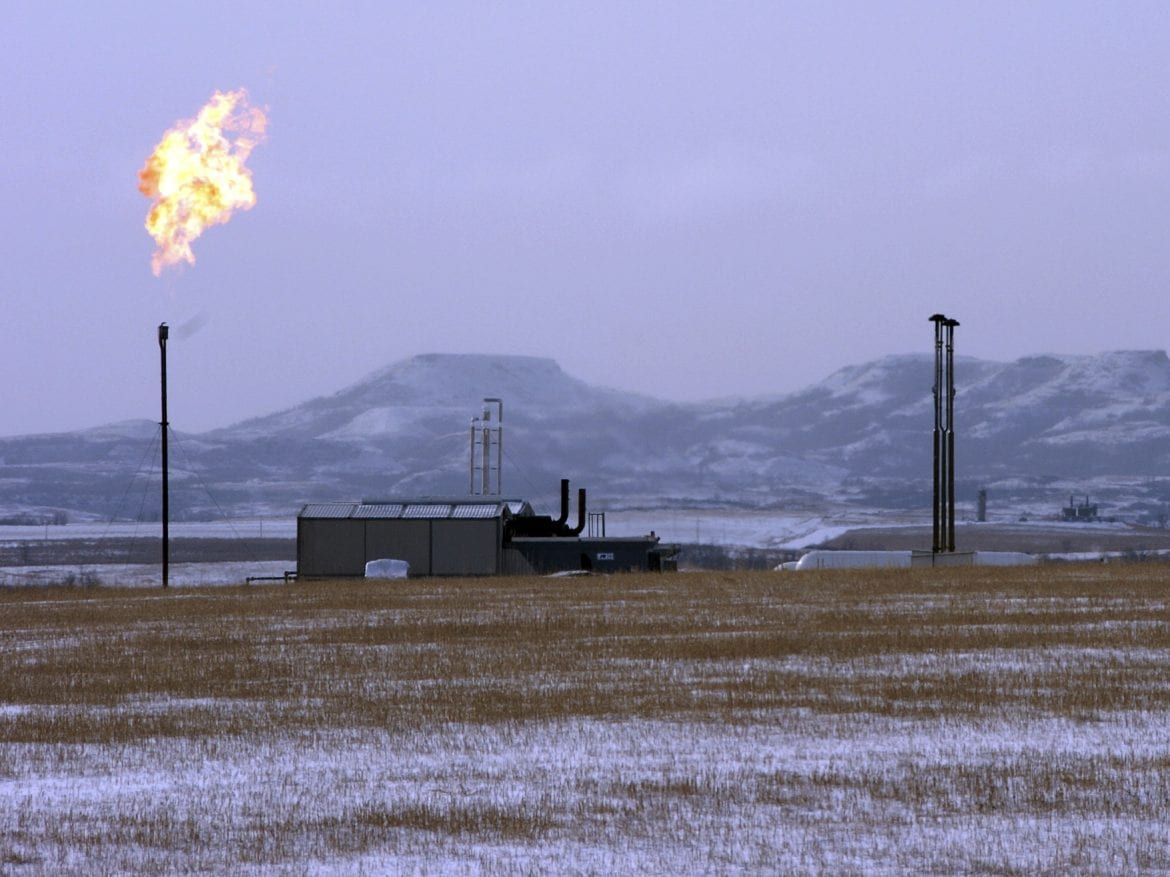 A gas flare is seen at a natural gas processing facility near Williston, N.D. in 2015. A new study says the amount of methane leaking is more than government estimates.