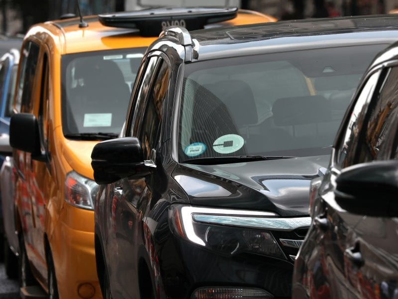 An Uber car drives in traffic on 6th Avenue in New York City on July 27. New York City became the first major U.S. city to limit ride-hailing services.
