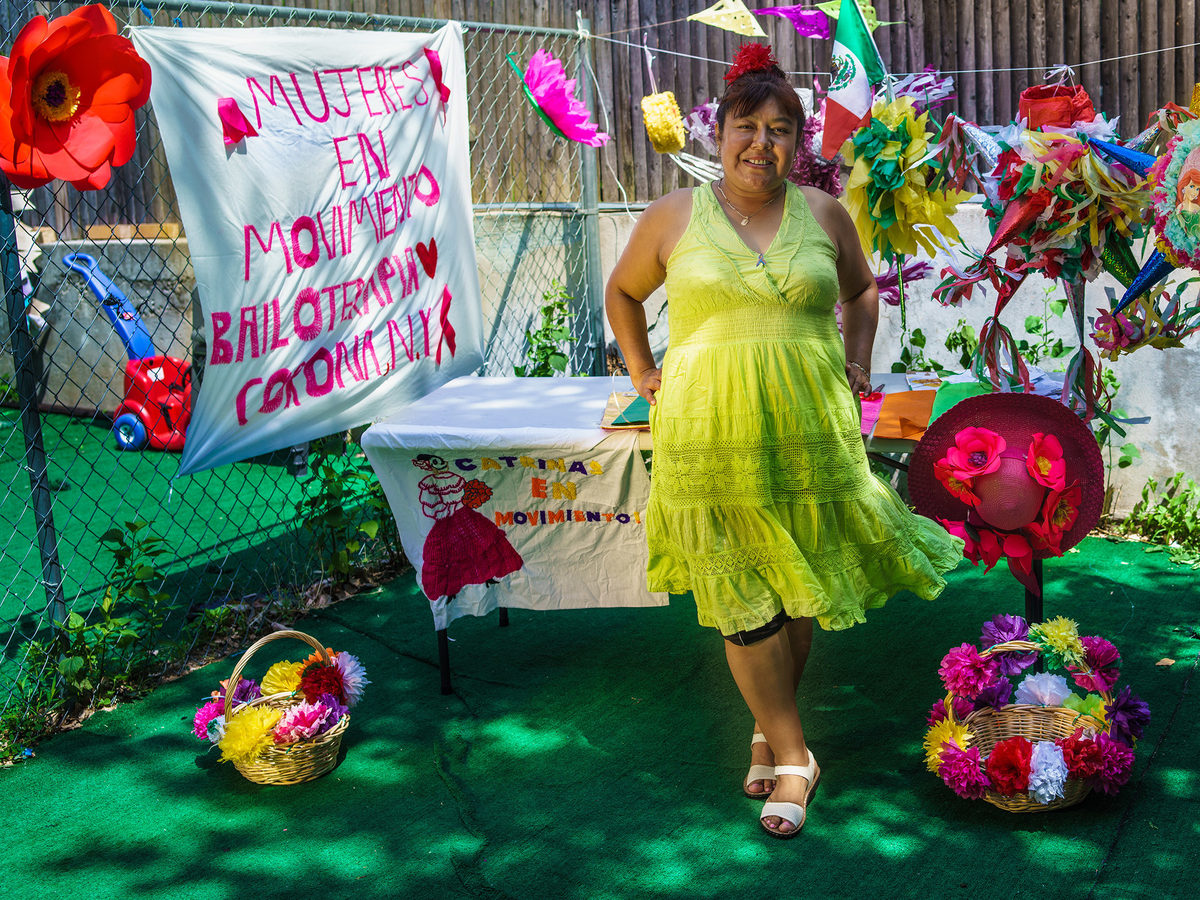 A portrait of Valeria Reyes among her handcrafted piñatas. Originally from Mexico, Reyes is a member of the group Mujeres en Movimiento, which explores the use of dance, art, ancestral remedies and civic engagement to empower Latina immigrant women in Corona, Queens.