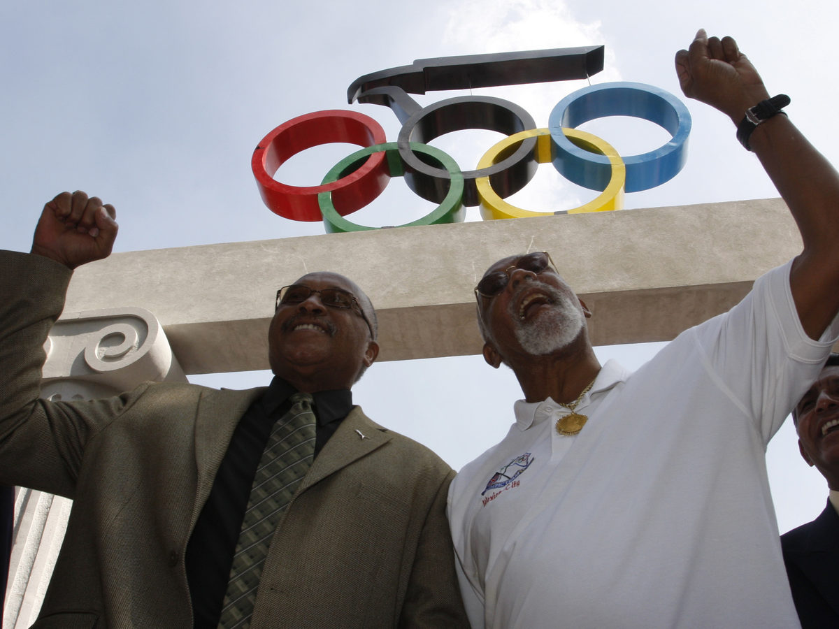 U.S. Olympic medalists Tommie Smith, left, and John Carlos hold up their fists at the Mexican Olympic Committee building in Mexico City, Wednesday, Oct. 15, 2008.