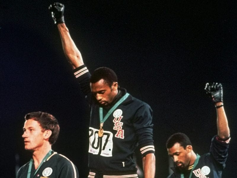 Extending gloved hands skyward in racial protest, U.S. athletes Tommie Smith, center, and John Carlos stare downward during the playing of the Star Spangled Banner at the Summer Olympic Games in Mexico City on Oct. 16, 1968.