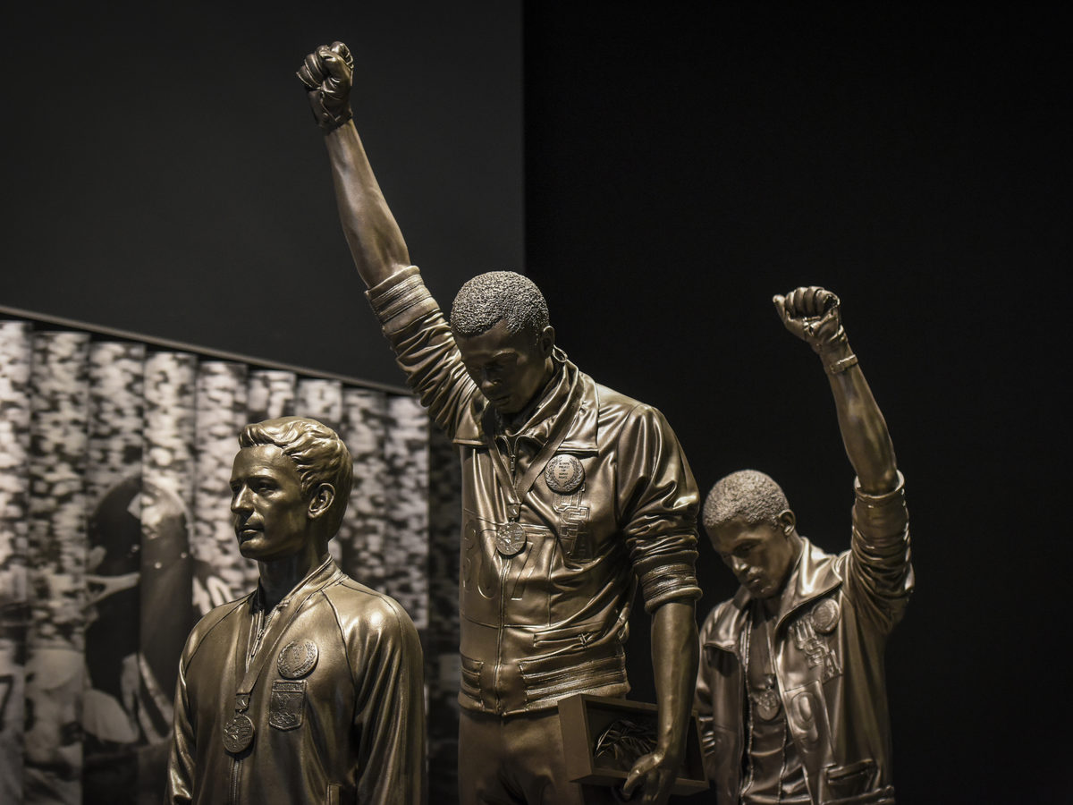 A statue depicting USA track and field athletes Tommie Smith, C, and John Carlos, R, as they raised gloved fists during their medal ceremony at the 1968 Summer Olympics is housed in the Sports Galleries at the Smithsonian Institute's National Museum of African American History and Culture.