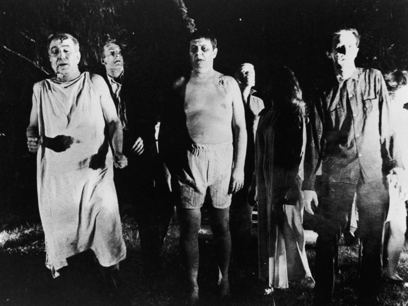 A line of undead 'zombies' walk through a field in the night in a still from the film, 'Night Of The Living Dead,' directed by George Romero, 1968. The film has been reissued for screenings on the 50th anniversary of its release.