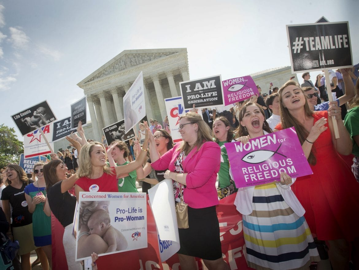 In this 2014 photo, demonstrators react to hearing the Supreme Court's decision on the Hobby Lobby birth control case outside the Supreme Court in Washington. A judge in California has blocked implementation of a Trump administration policy that would let more employers decline to offer birth control coverage on religious or moral grounds.