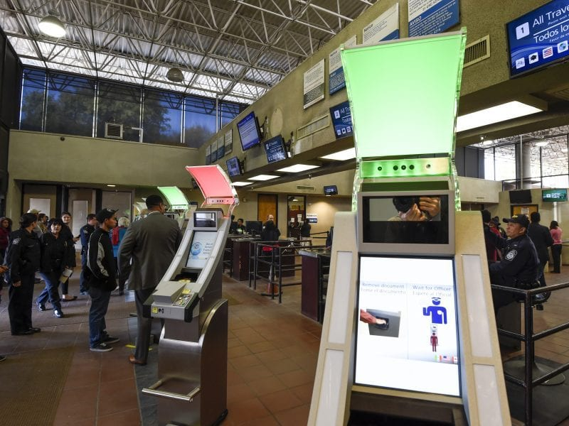 Pedestrians crossing from Mexico into the United States at the Otay Mesa Port of Entry wait to use biometric kiosks in San Diego. A new study says visa overstays exceeded illegal border crossings.