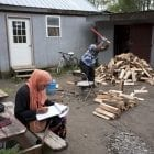 Seen in 2017, a girl studies for school while a man chops wood in the Muslim enclave of Islamberg in Tompkins, N.Y. Four people have been arrested in an alleged plot to attack the community.