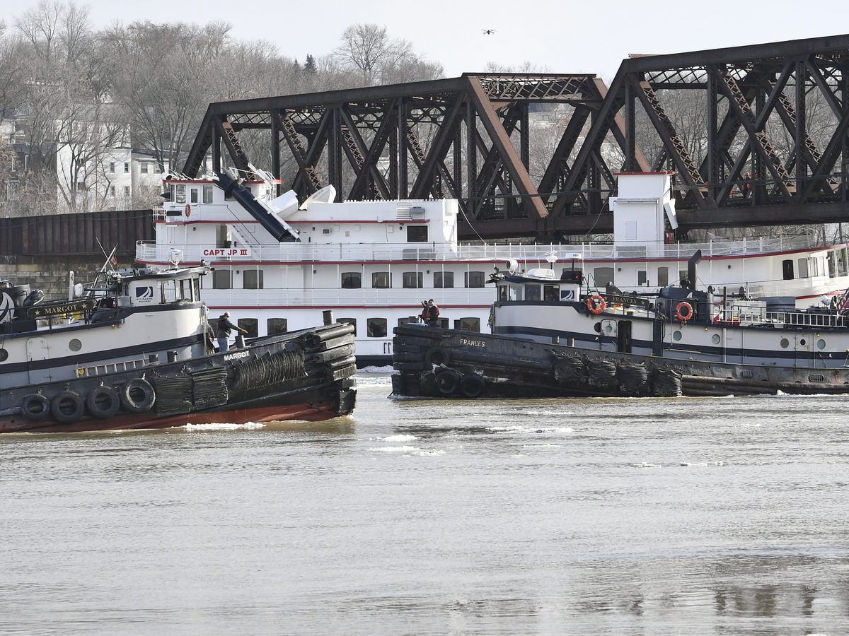 Tugboats work to free the Captain JP III cruise ship Friday.