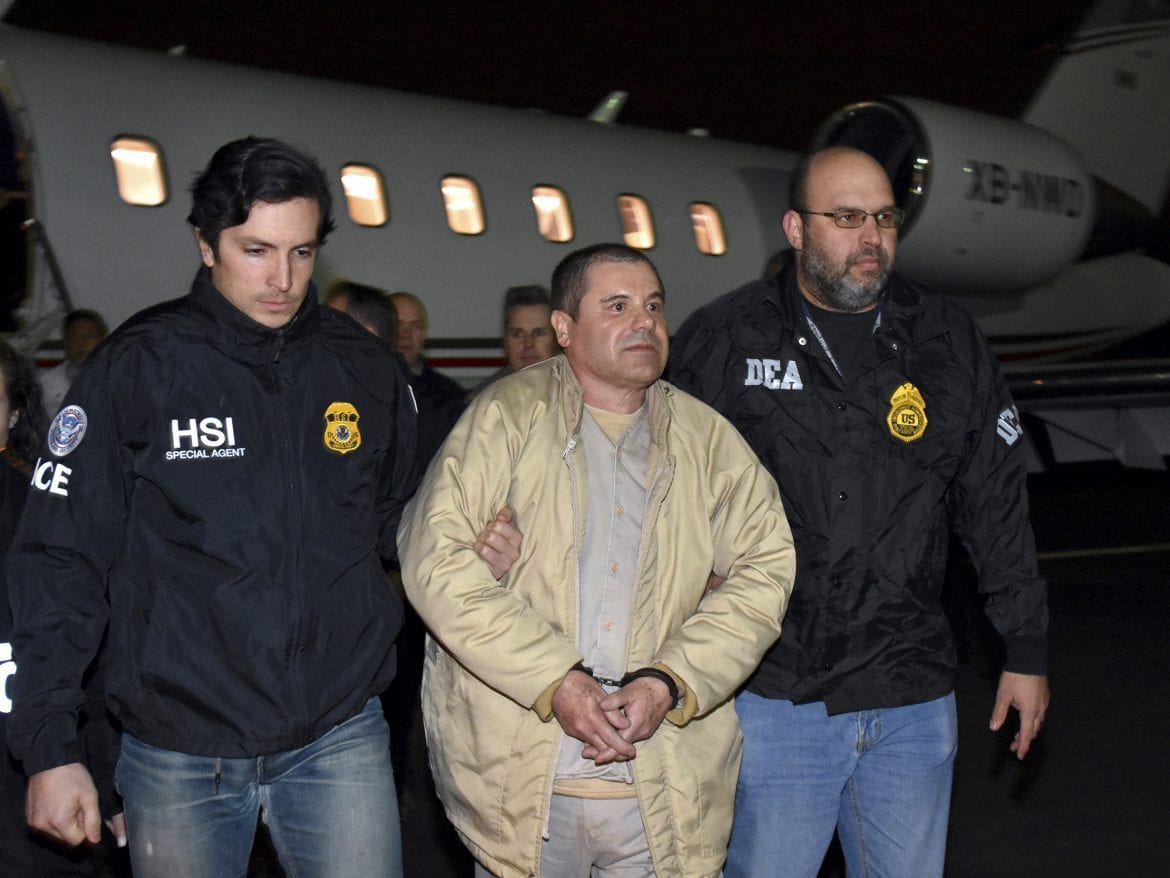 "U.S. law enforcement personnel escort Joaquín ""El Chapo"" Guzmán from a plane to a waiting caravan of SUVs at New York's Long Island MacArthur Airport in January 2017."