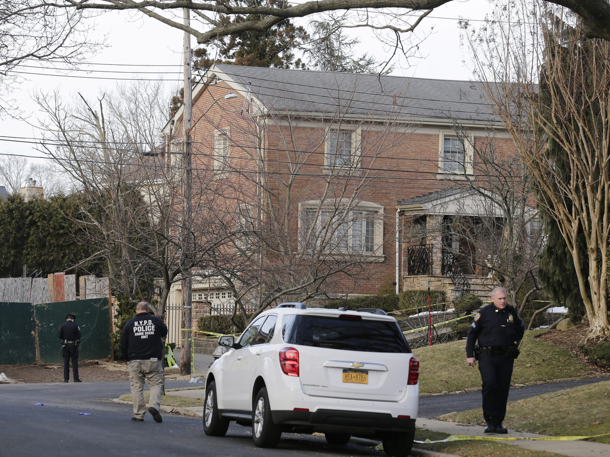"""Police walk near the scene where reputed leader of the Gambino crime family Francesco """"Frank"""" Cali, 53, was fatally shot Wednesday night."""