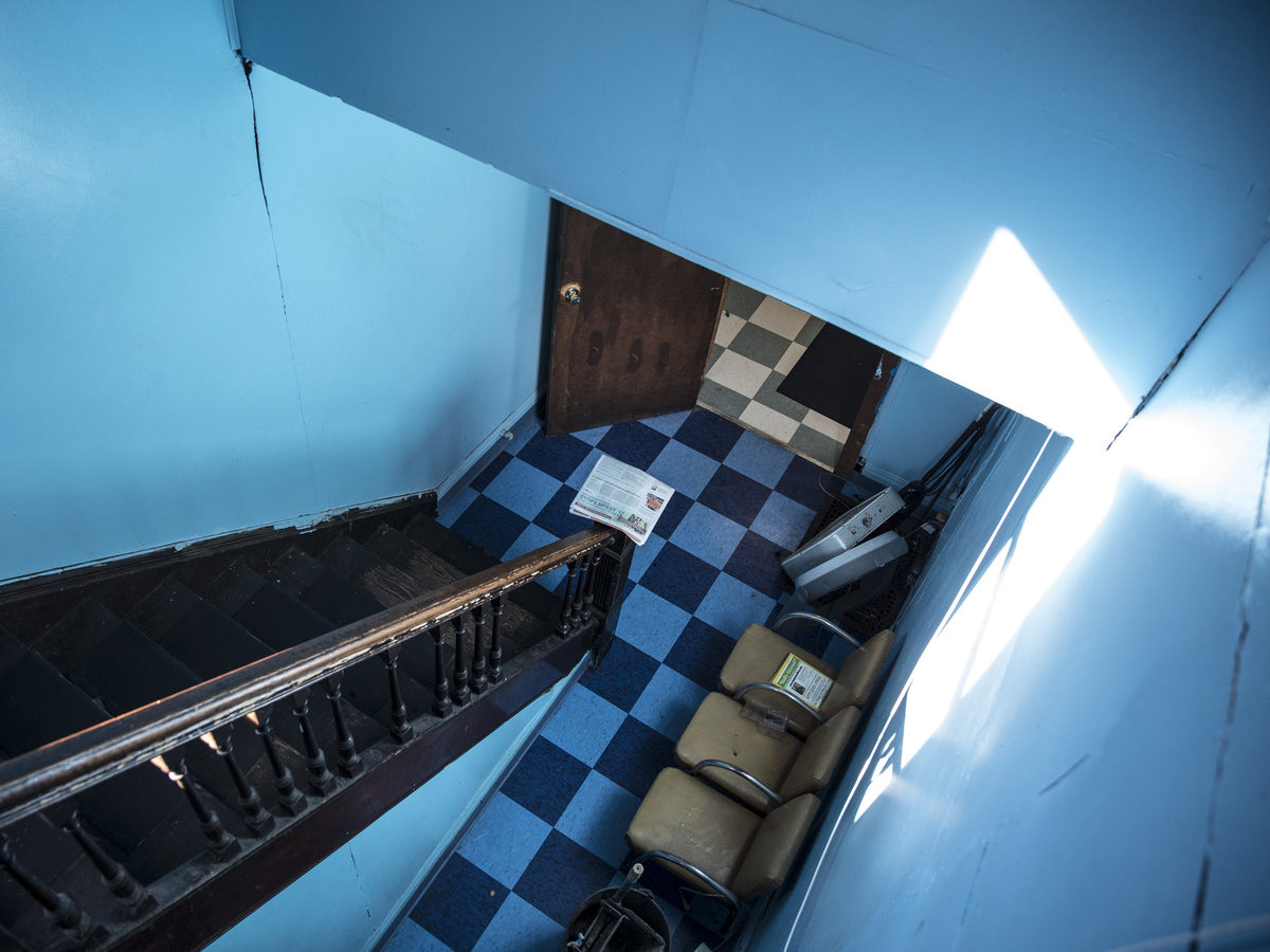 The barbershop's hallway provides access to the beauty shop upstairs.