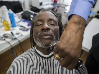 Charleston trims Melvin Rutledge's beard during the One Haircut at a Time event at the Emma L. Johnston Southside Family Resource Center.