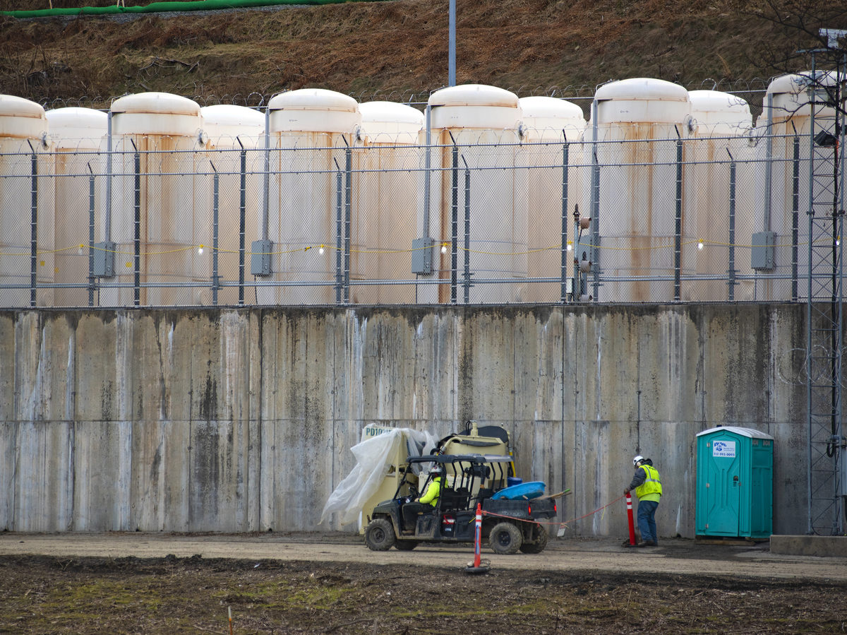 Once it is safe to remove the spent fuel from the pool, it's stored outside in white, metal casks. They are lined up on a concrete base behind razor wire, against a hillside near the power plant.