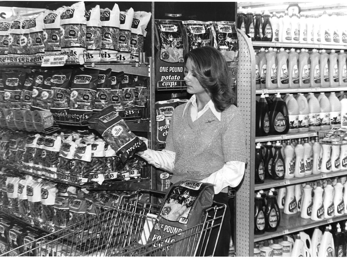 A woman shopping in the 1970s picks up a bag of Snyder's pretzels. Today, Hanover remains a center of snack food manufacturing, even as the food industry changes around it.