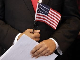A newly sworn-in U.S. citizen holds a U.S. flag and documents during a naturalization ceremony in 2018 at the John F. Kennedy Presidential Library and Museum in Boston.