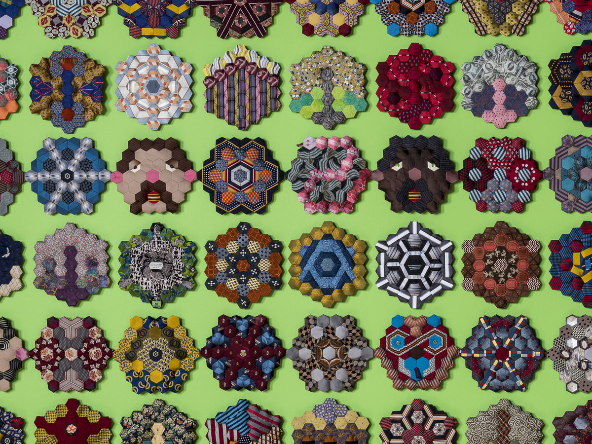 """Each of these vignettes required 37 """"hexies,"""" little hexagonal scraps cut from donated neckties."""