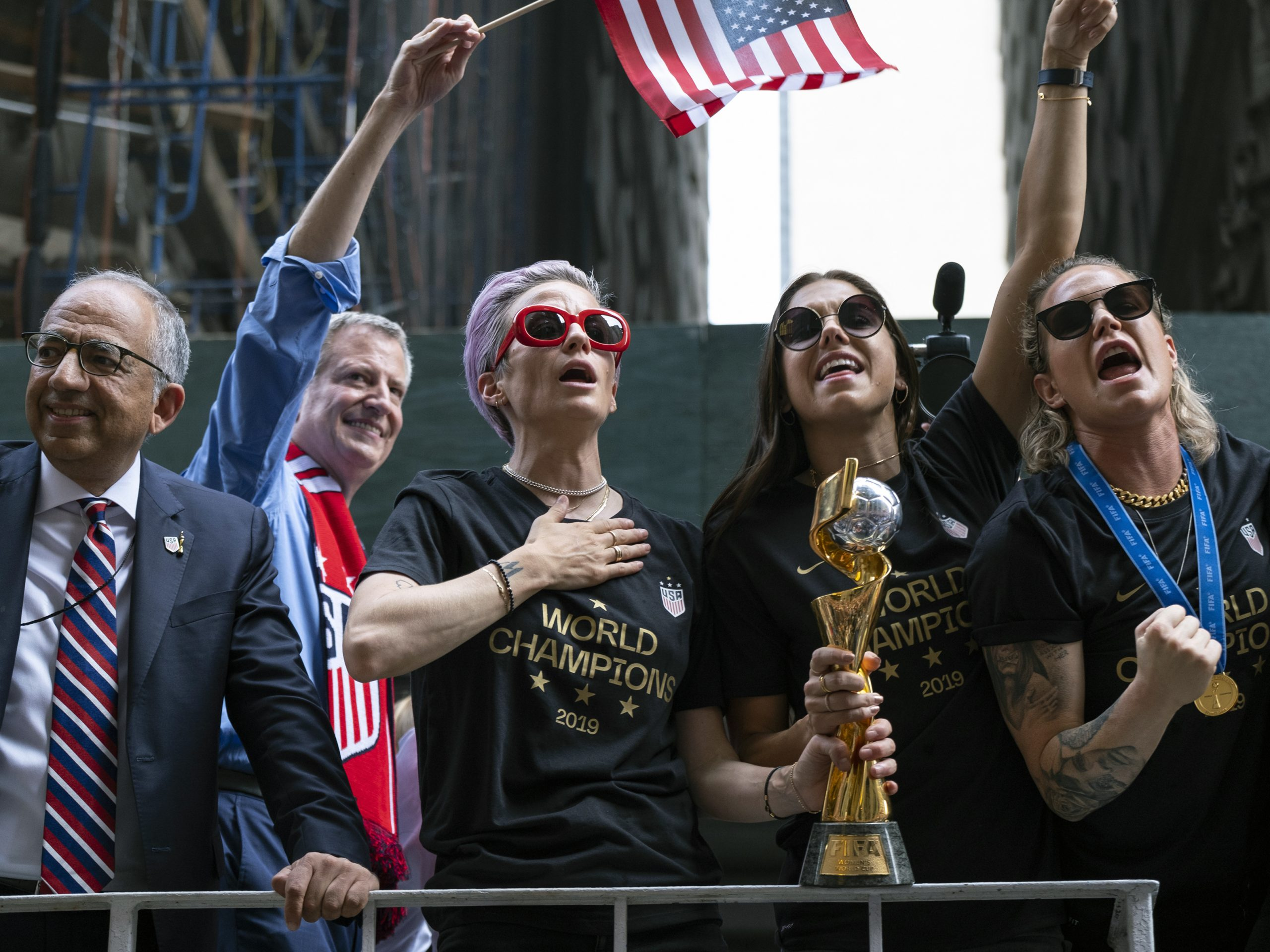 From left, U.S. Soccer Federation President Carlos Cordeiro, New York Mayor Bill de Blasio and soccer players Megan Rapinoe, Alex Morgan and Ashlyn Harris celebrate the U.S. women's soccer team's world championship in New York, during a ticker tape parade along the Canyon of Heroes Wednesday.