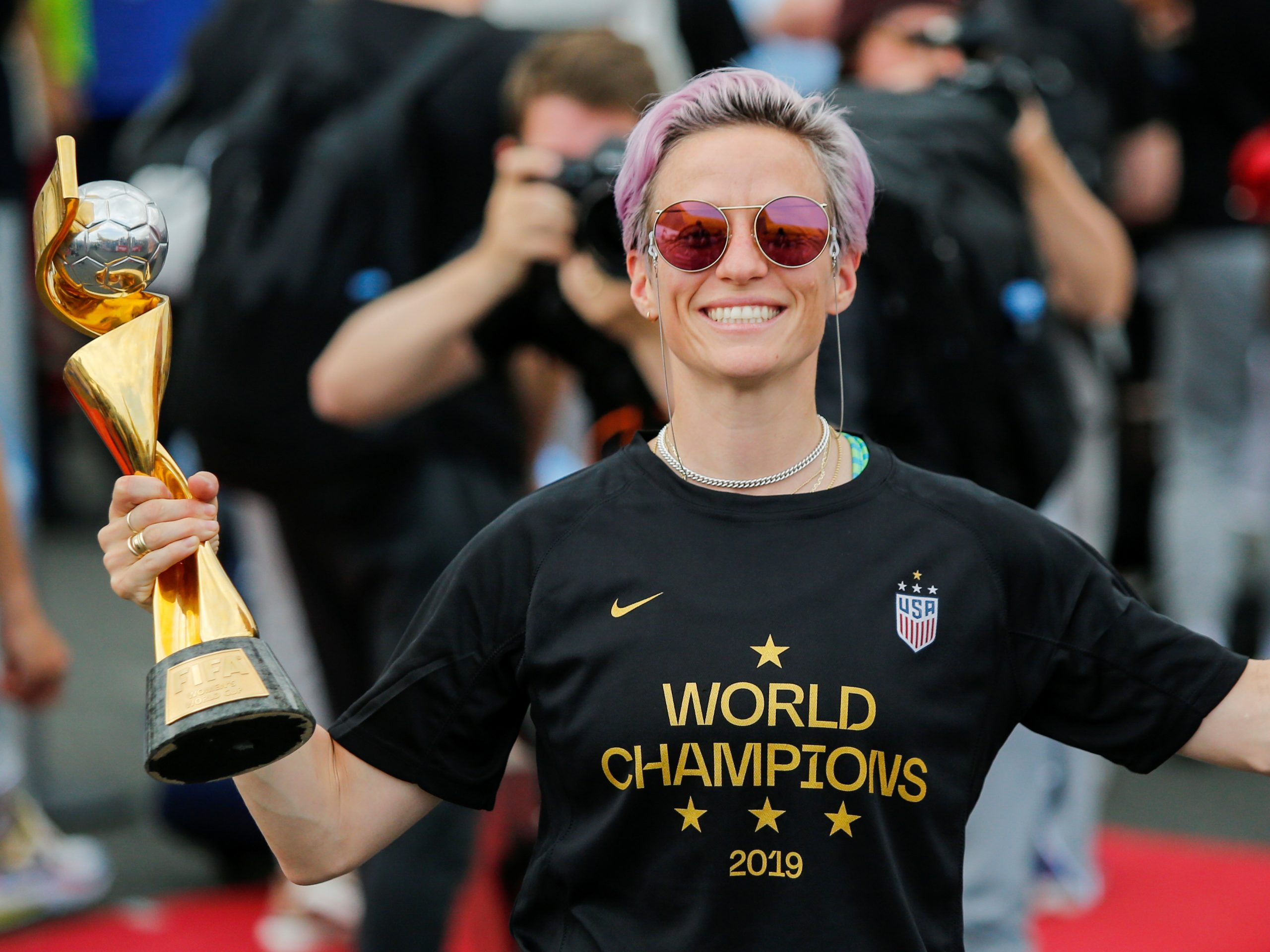 The U.S. Women's National Team is being honored by a ticker tape parade in New York Wednesday. Here, Megan Rapinoe smiles as she holds the FIFA Women's World Cup trophy as the team arrives at the Newark International Airport.
