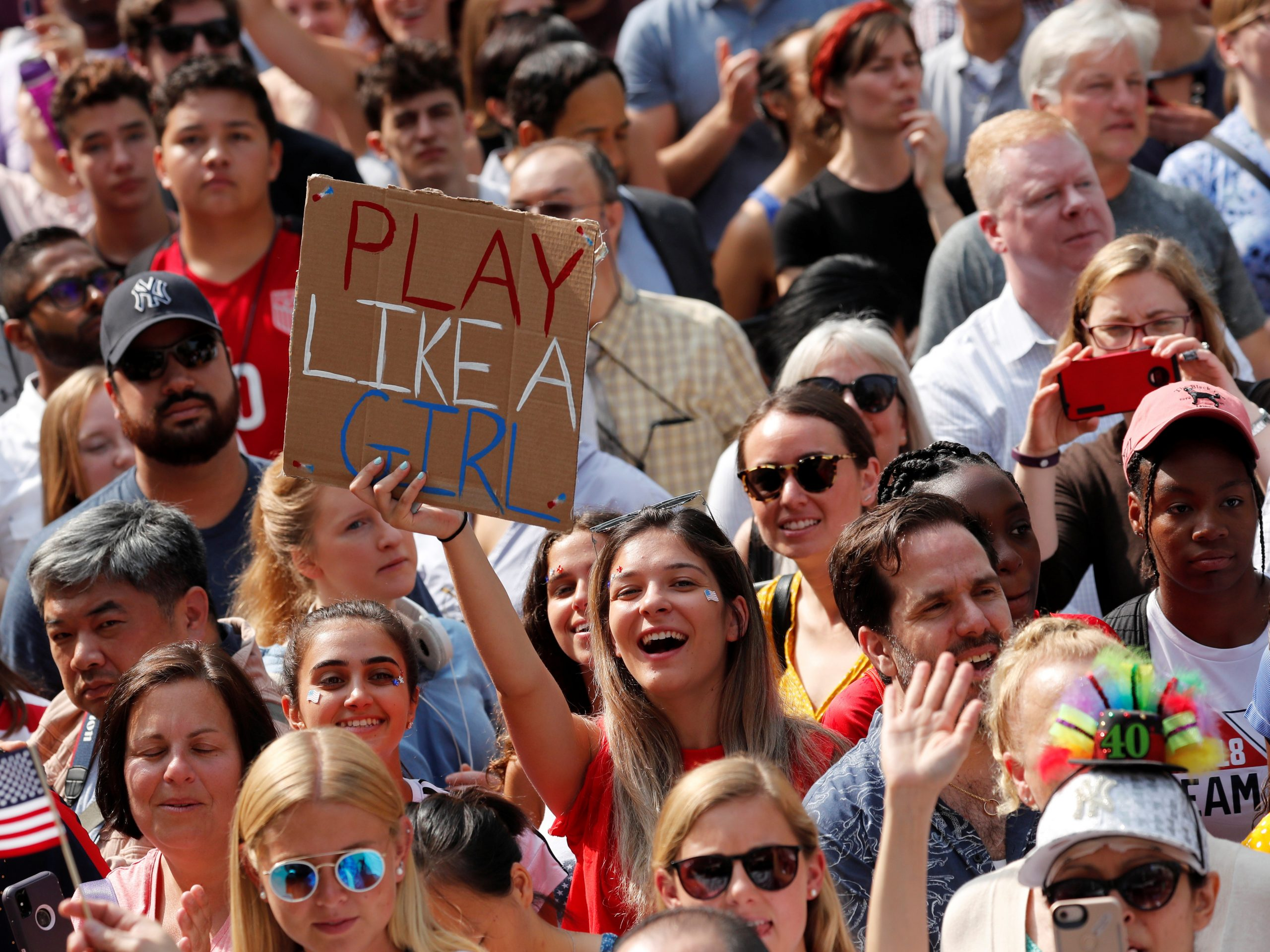 Fans of the U.S. Women's National Team cheer as the World Cup champions parade up Broadway in New York Wednesday.