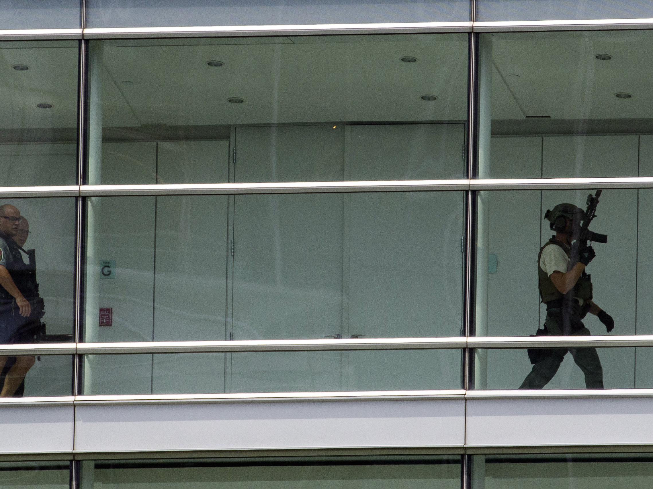 Law enforcement officers search one of the buildings that house Gannett and USA Today on Wednesday. No gunman was found.