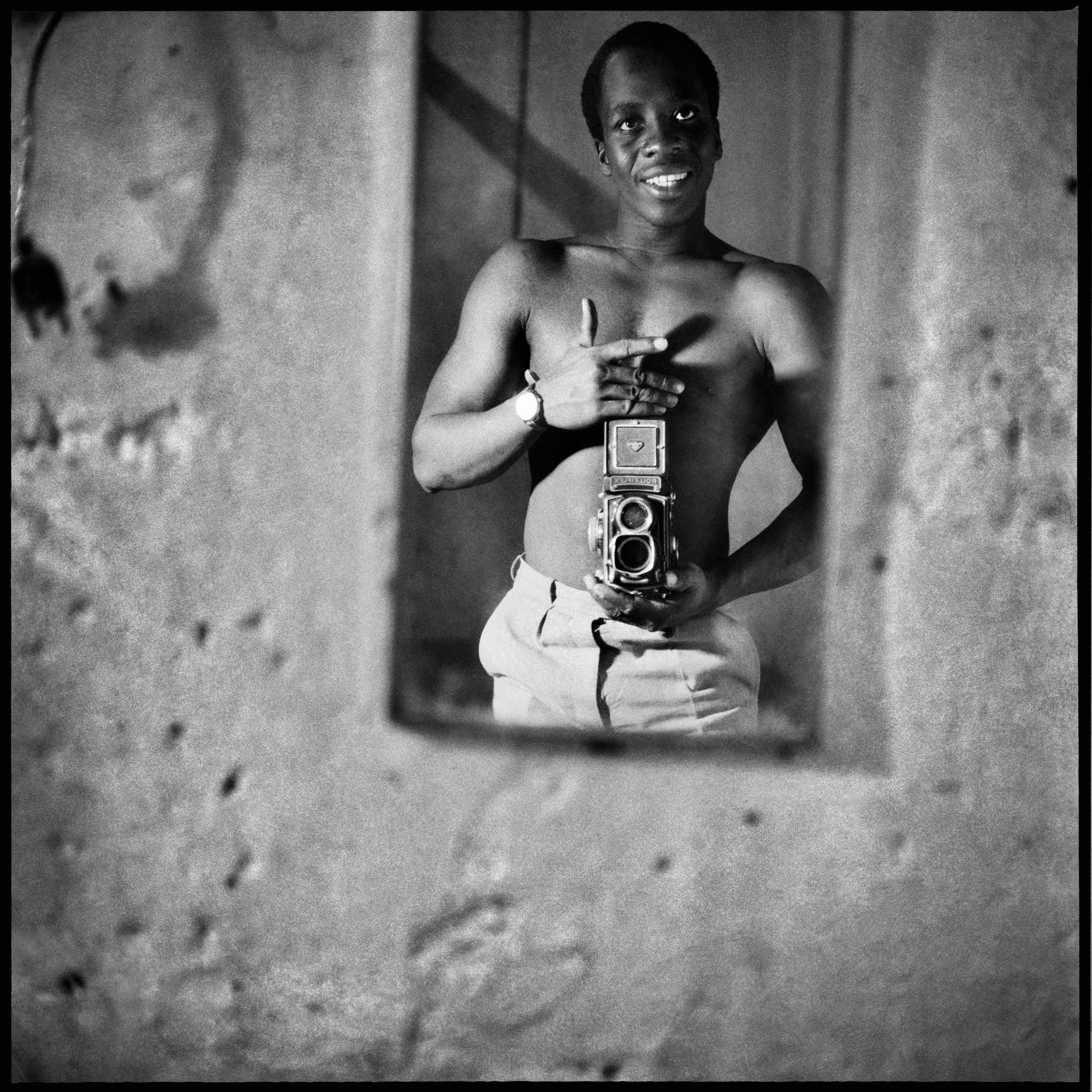 """Sanle Sory took """"autoportraits"""" as in this selfie showing off his Rolleiflex camera. He was born in 1943 in what was still colonial Upper Volta and is now the country of Burkina Faso. His black-and-white portraits show the old meeting the new: families posing in Western garb, young people side by side with a boom box and a traditional African stringed instrument."""