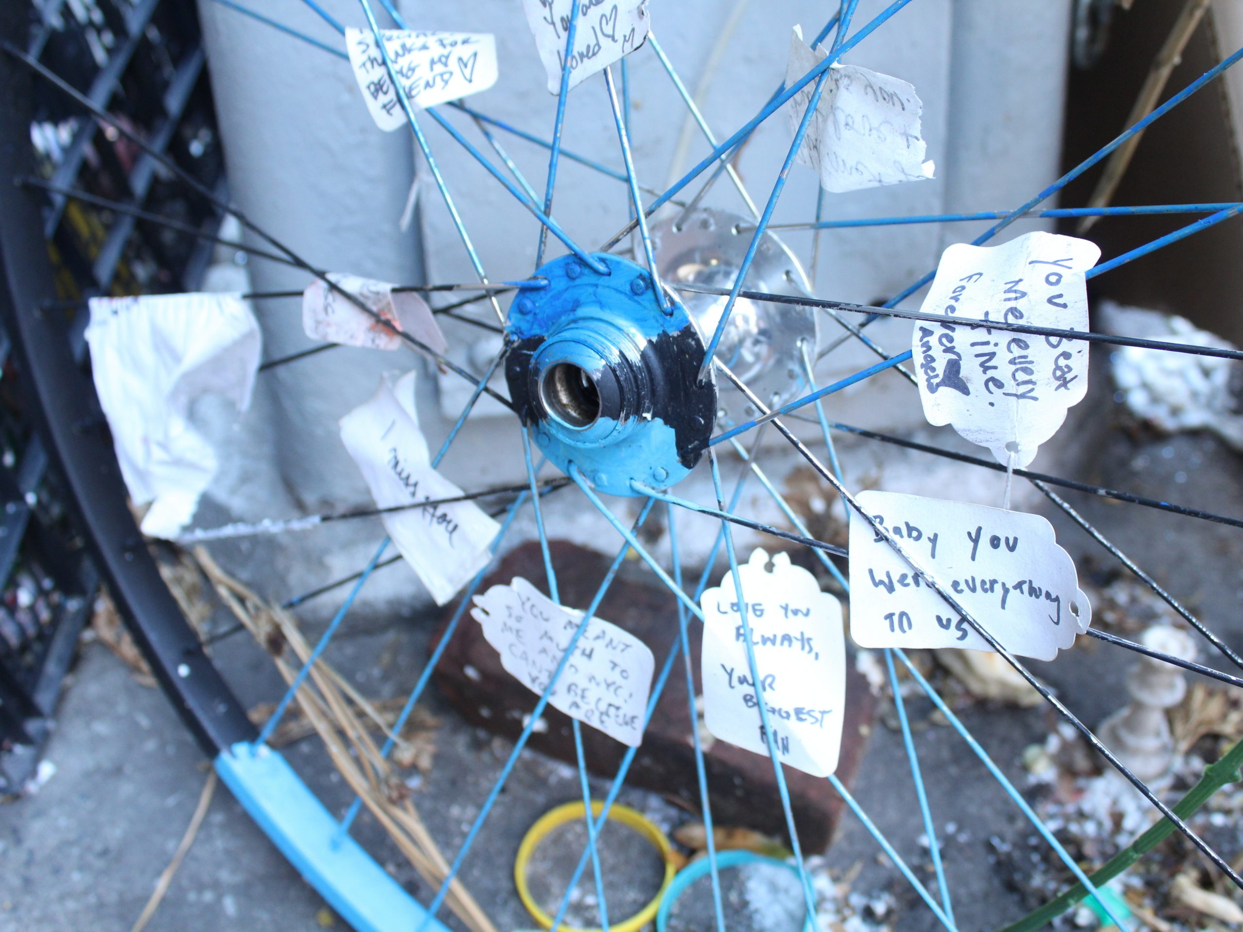 A memorial site in Manhattan, where Robyn Hightman, a bike messenger was hit and killed by a truck this summer. People have tucked messages of support in the spokes of a bike wheel.