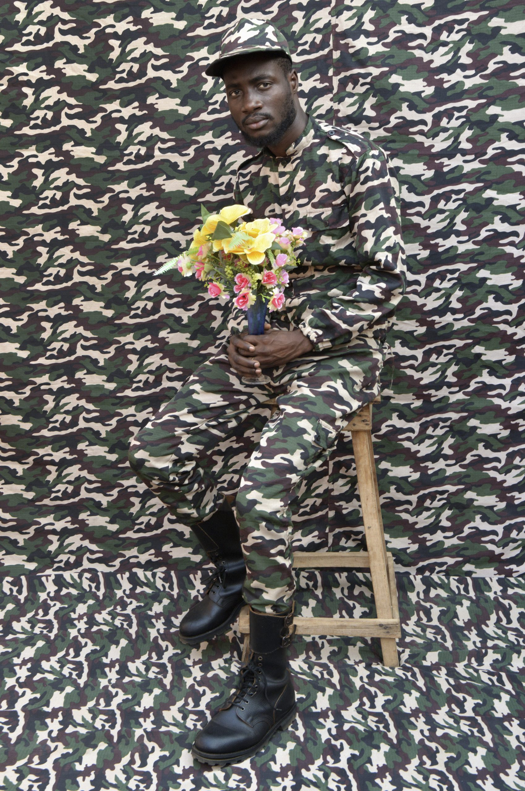 """Born in 1965 in Porto Novo, Benin, Leonce Raphael Agbodjelelou """"draws inspiration from growing up working in his father Joseph's prestigious studio and casts models in place of paying clientele,"""" says Yossi Milo, who curated the exhibit. Here, military camouflage pattern seems to merge subject and backdrop into one even while colorful flowers burst out of the background."""