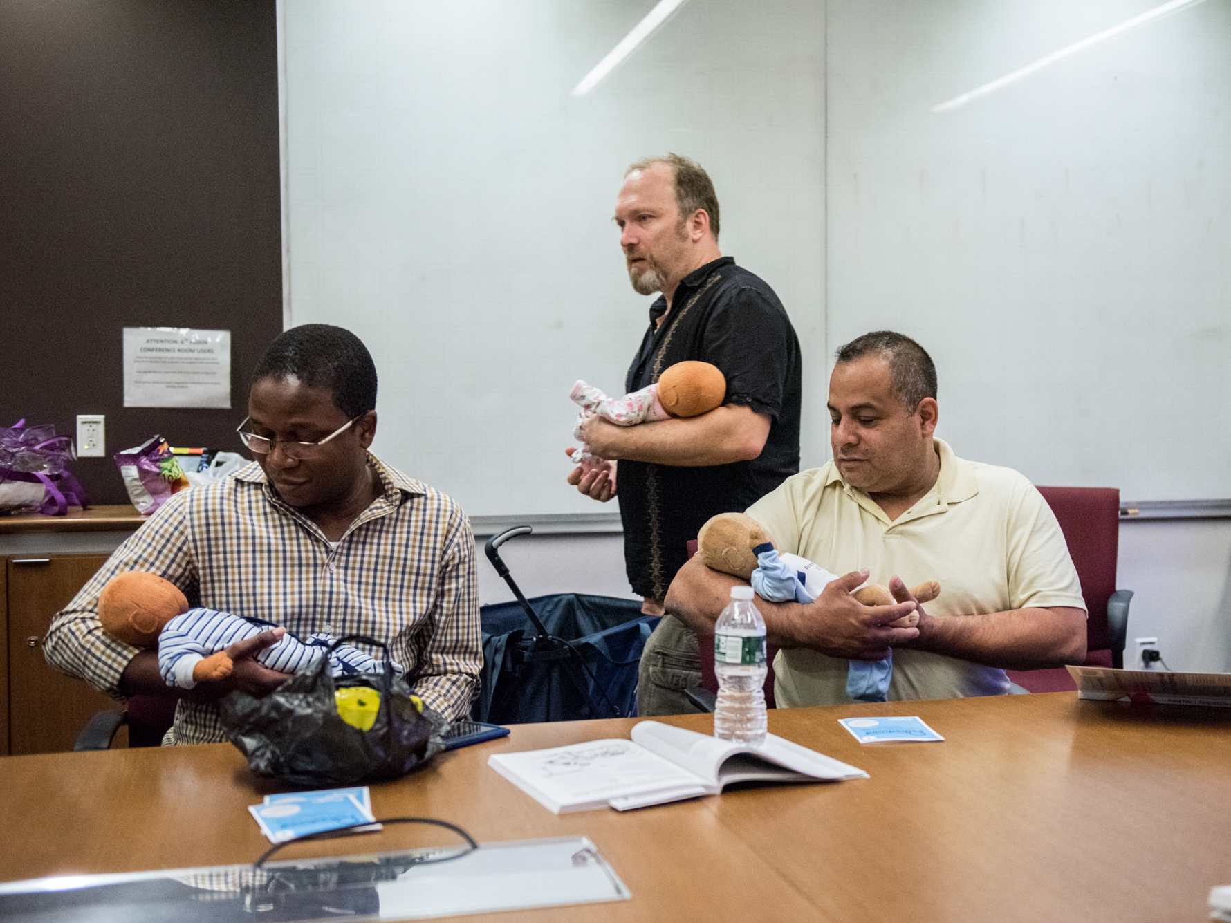 """Joe Bay (center), coach of a New York City """"Bootcamp for New Dads,"""" instructs Adewale Oshodi (left) and George Pasco in how to cradle an infant for best soothing."""