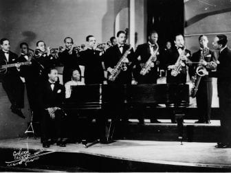Andy Kirk And His Orchestra, including Mary Lou Williams (sitting at the piano), pose for a studio group portrait in 1940. Williams toured with Kirk's band before settling in New York.