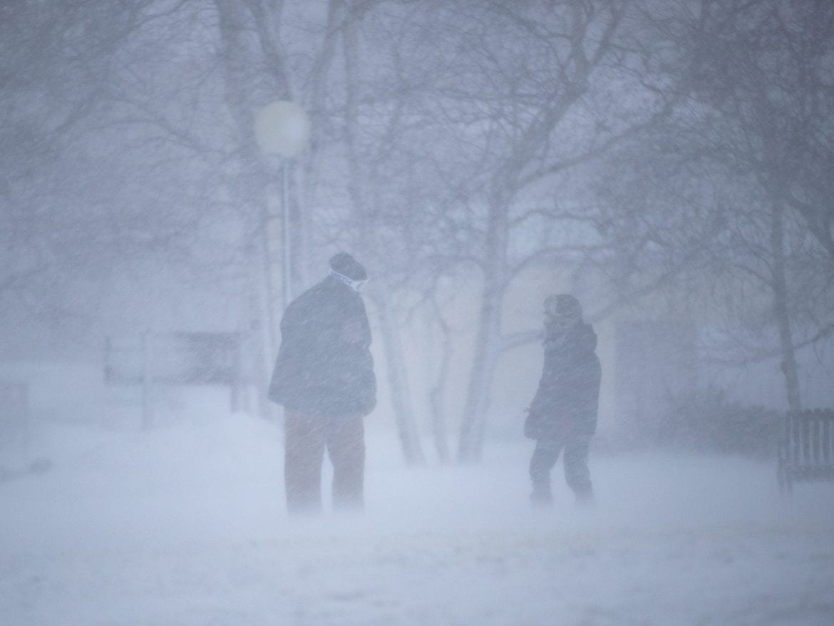 Two people braving blizzard conditions in Duluth, Minn., on Saturday.