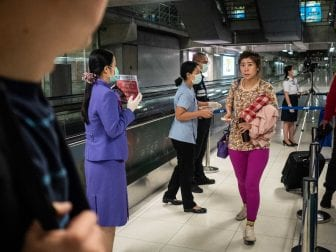 Three U.S. airports are now screening passengers from Wuhan, China, for coronavirus. Above: Public health officials hand out disease-monitoring information after performing thermal scans on passengers arriving from Wuhan at the international airport in Bangkok, Thailand.