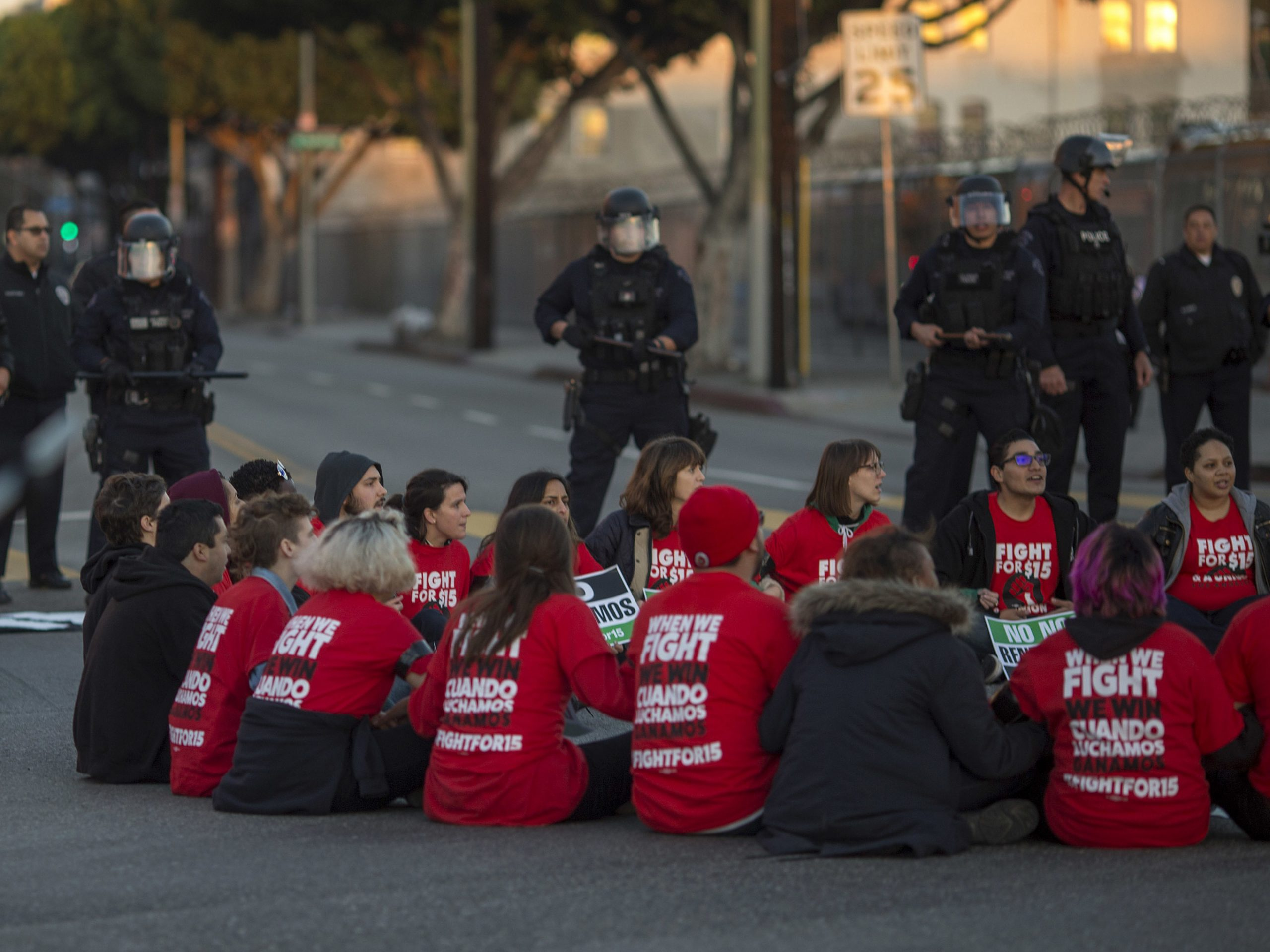 Police surround striking McDonald's workers sitting in an intersection in Los Angeles, demanding a $15 per hour wage and union rights during nationwide 'Fight for $15 Day of Disruption' in November 2016.