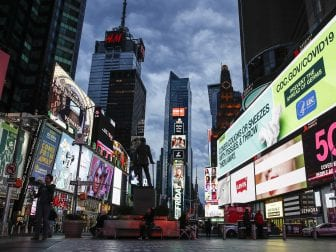 A screen displaying messages concerning COVID-19 is seen in a sparsely populated Times Square in New York City on Friday. New York Gov. Andrew Cuomo has ordered all nonessential businesses to close by Sunday.