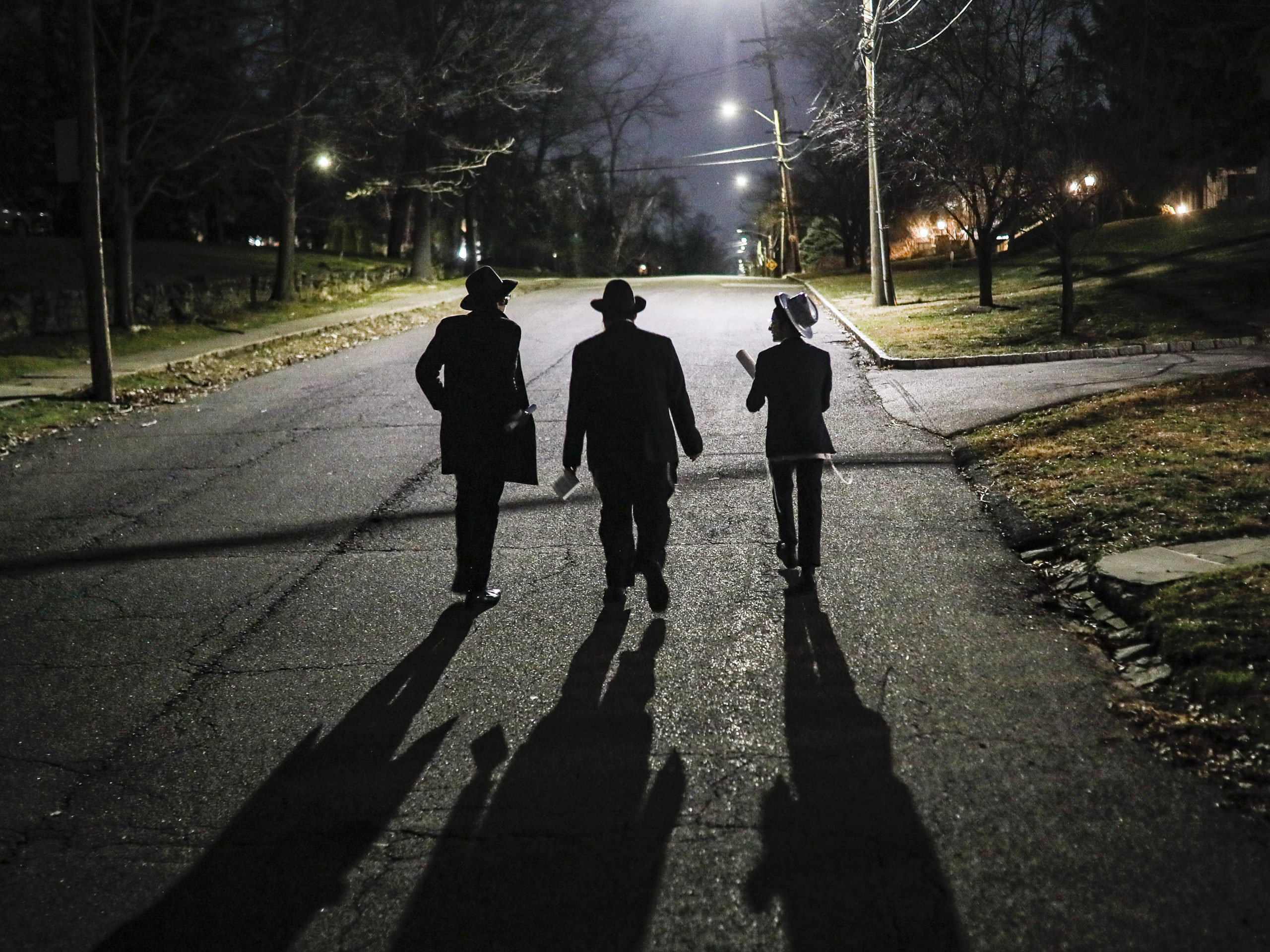 Student volunteers walk through New Rochelle to perform a Purim reading at homes on Monday. Some residents there are already under self-quarantine.
